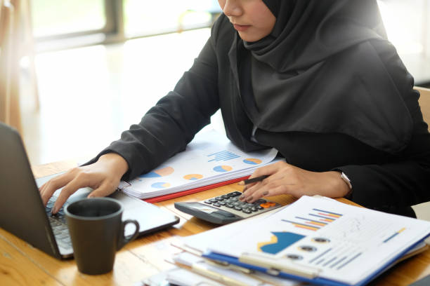 Attractive female Arabic corporate worker working on laptop computer on desk stock photo