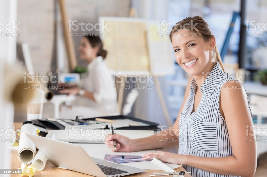 An attractive mid adult female architect pauses from working at her...
