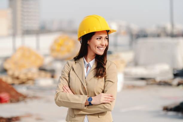 atractiva arquitecta con cabello castaño, sonrisa toothy, casco en la cabeza y vestido informal elegante de pie en el sitio de construcción con los brazos cruzados. - arquitecta fotografías e imágenes de stock