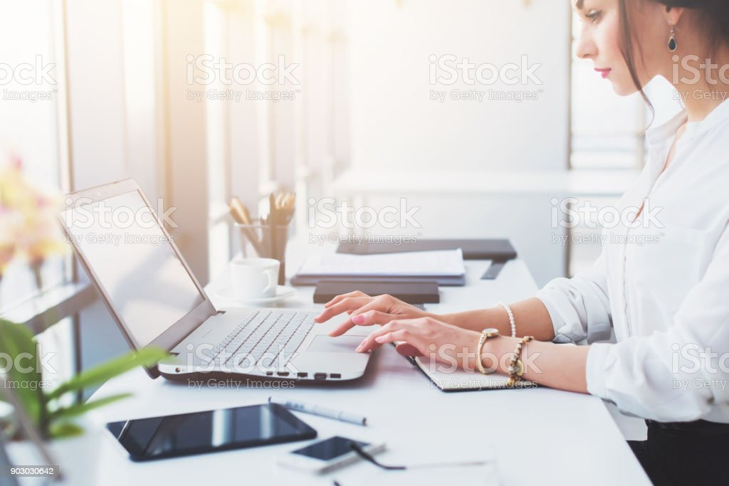 Attractive female assistant working, typing, using portable computer, concentrated, looking at the monitor. Office worker reading business e-mail. stock photo