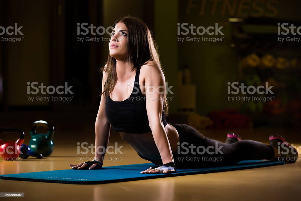 Attractive female athlete stretching on yoga mat in gym royalty-free stock photo