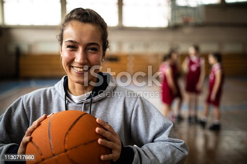 Young beautiful female basketball coach standing in school gym , holding basketball ball , looking at camera and smiling