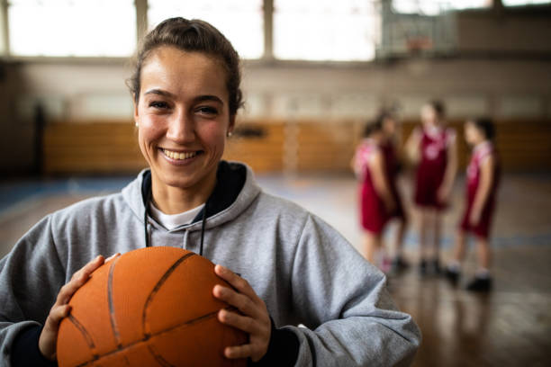 Attractive female basketball coach Young beautiful female basketball coach standing in school gym , holding basketball ball , looking at camera and smiling female high school student stock pictures, royalty-free photos & images