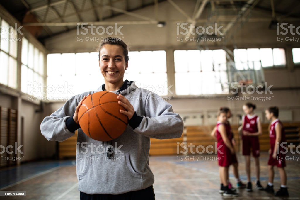 Young beautiful female basketball coach standing in school gym ,...