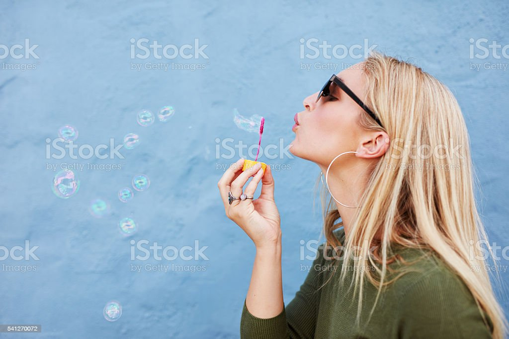 Attractive female blowing soap bubbles stock photo