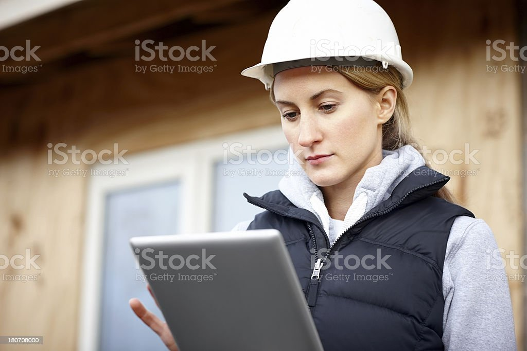 Attractive female construction worker with a tablet computer stock photo