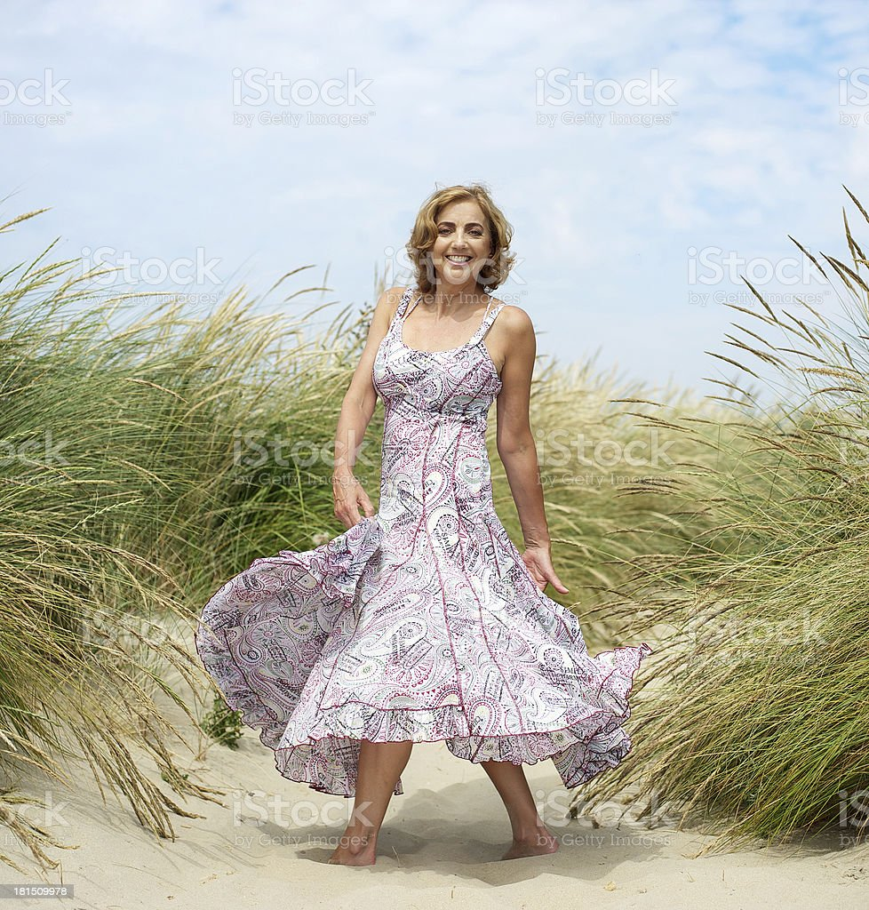 Attractive female dancing at the beach stock photo
