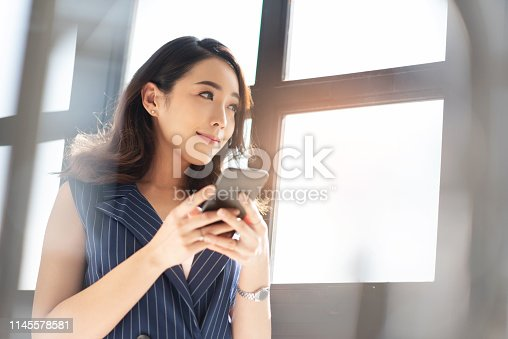 istock Attractive Female designer smiling and standing near a window. 1145578581