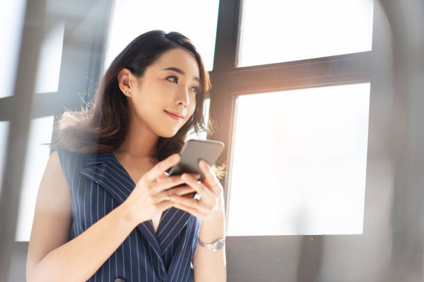 Attractive Female designer smiling and standing near a window. Modern Asian business woman is using cell phone in the office. Attractive Female designer smiling and standing near a window. japanese ethnicity stock pictures, royalty-free photos & images
