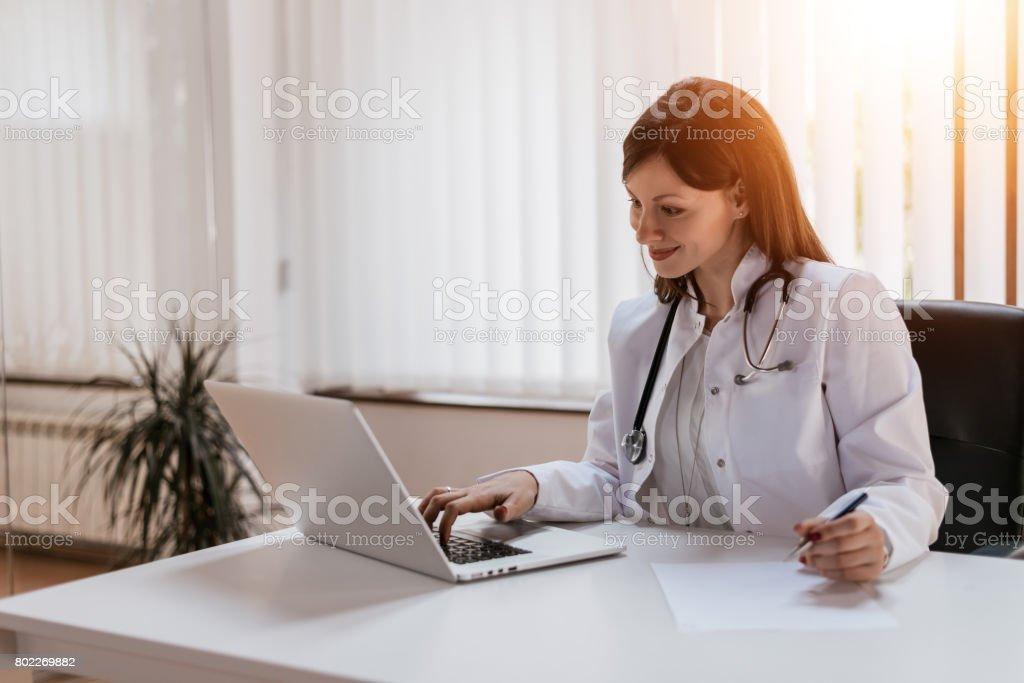 Attraktive Ärztin arbeiten mit Ihrem Laptop in Ihrem Büro – Foto