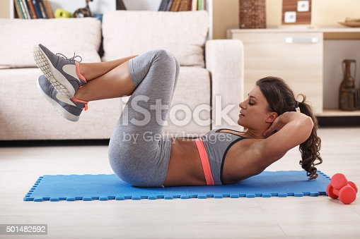 istock Attractive female doing exercise at home. 501482592
