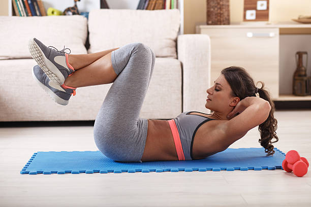 Attractive female doing exercise at home. stock photo