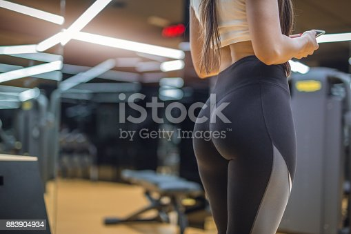 22 years old female fitness instructor is checking social media on her phone and resting from exercises