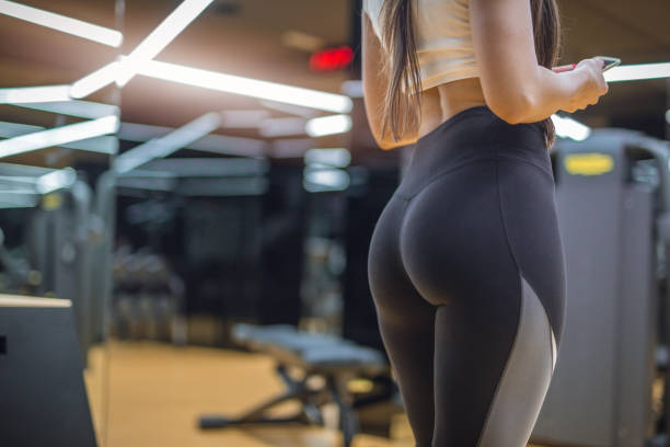 attractive female in a gym in a hot pants - buttock stock photos and pictures