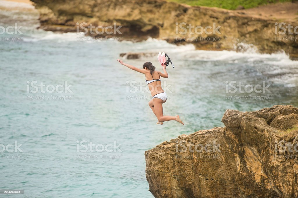 Attractive female jumping off cliff in Hawaii with snorkeling gear stock photo