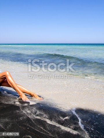 487881729 istock photo attractive female legs relaxing on a beautiful  beach 514080129