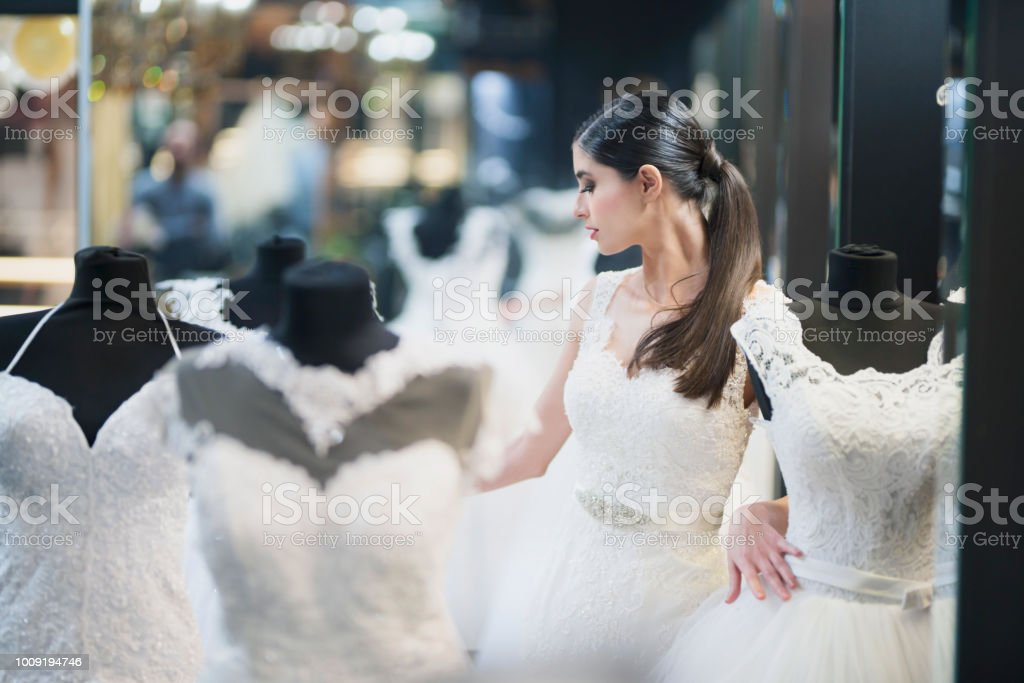 Attractive female looking wedding dresses stock photo