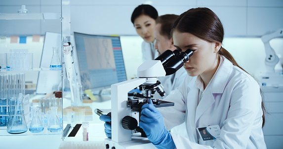 Female microbiologist studying pathogen with microscope. Multi ethnic research partner working in background