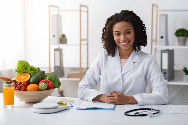 Attractive female nutritionist posing at her modern office stock photo