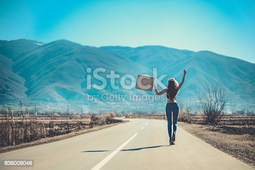 istock Attractive Female on Empty Road Hitchhiking with Raised Blank Sign Board 836009046