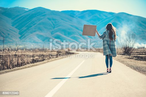 istock Attractive Female on Empty Road Hitchhiking with Raised Blank Sign Board 836012040