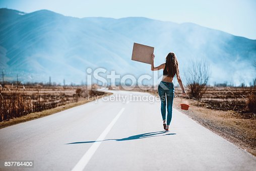 istock Attractive Female on Empty Road Hitchhiking with Raised Blank Sign Board 837764400