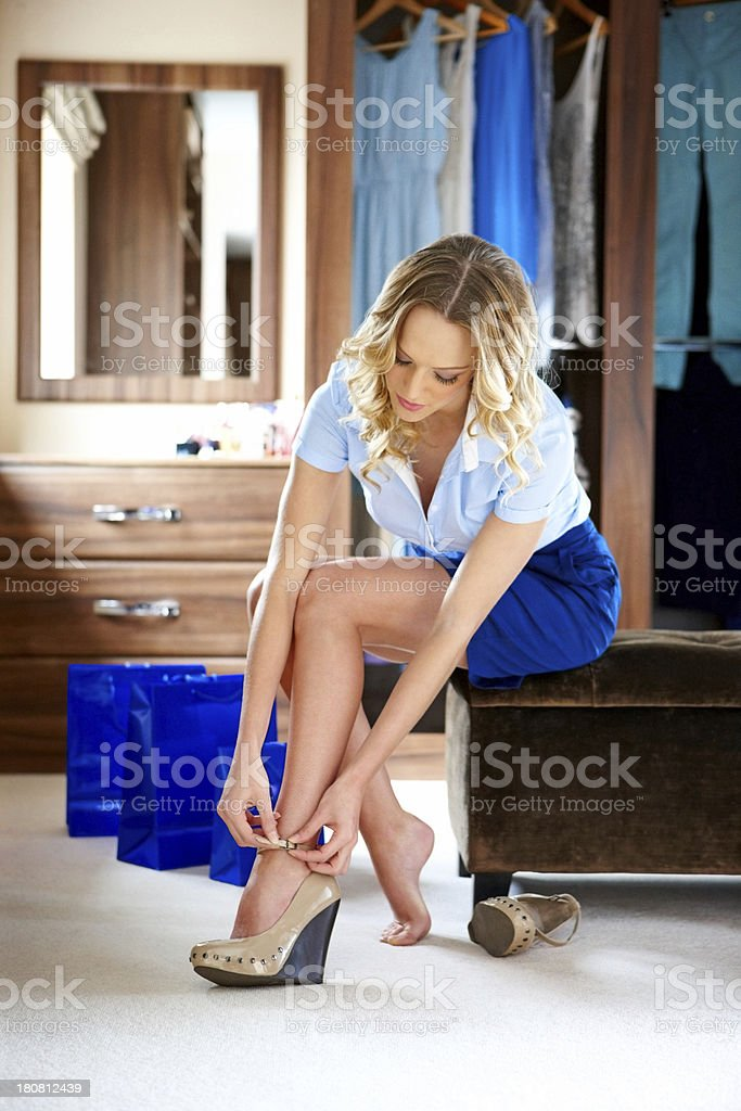 Attractive female putting on a pair of shoes at home stock photo