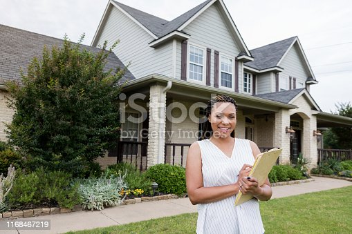 The attractive mid adult female realtor checks a home she has listed for sale.
