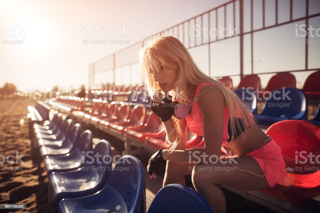 Attractive female runner seated on the beach resting after intensive volleyball game, female runner on the summer background royalty-free stock photo