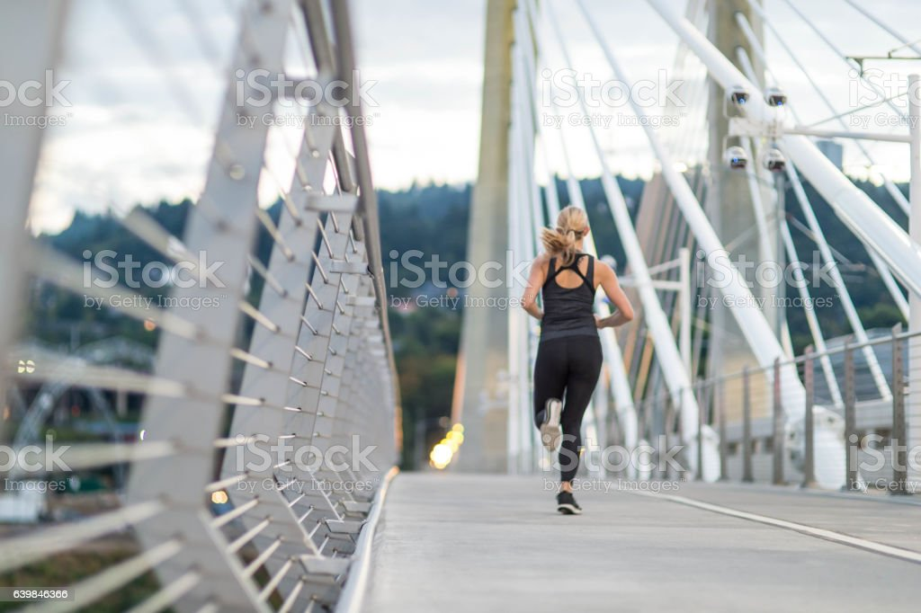 Attractive female running in the city across a pedestrian bridge stock photo