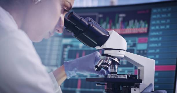 Attractive female scientist during research. Using microscope in futuristic lab stock photo