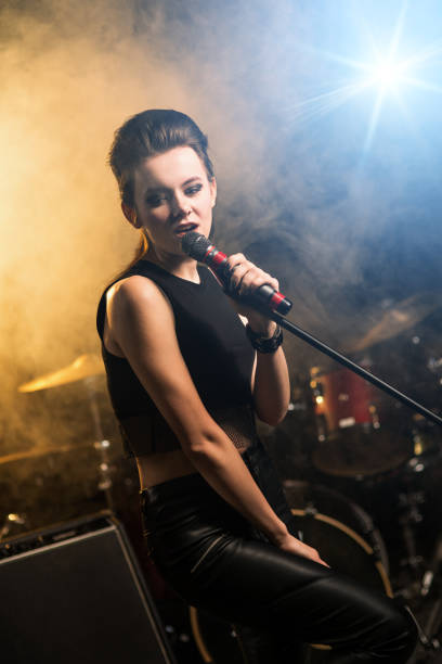 Attractive female singer on stage, rock concert stock photo