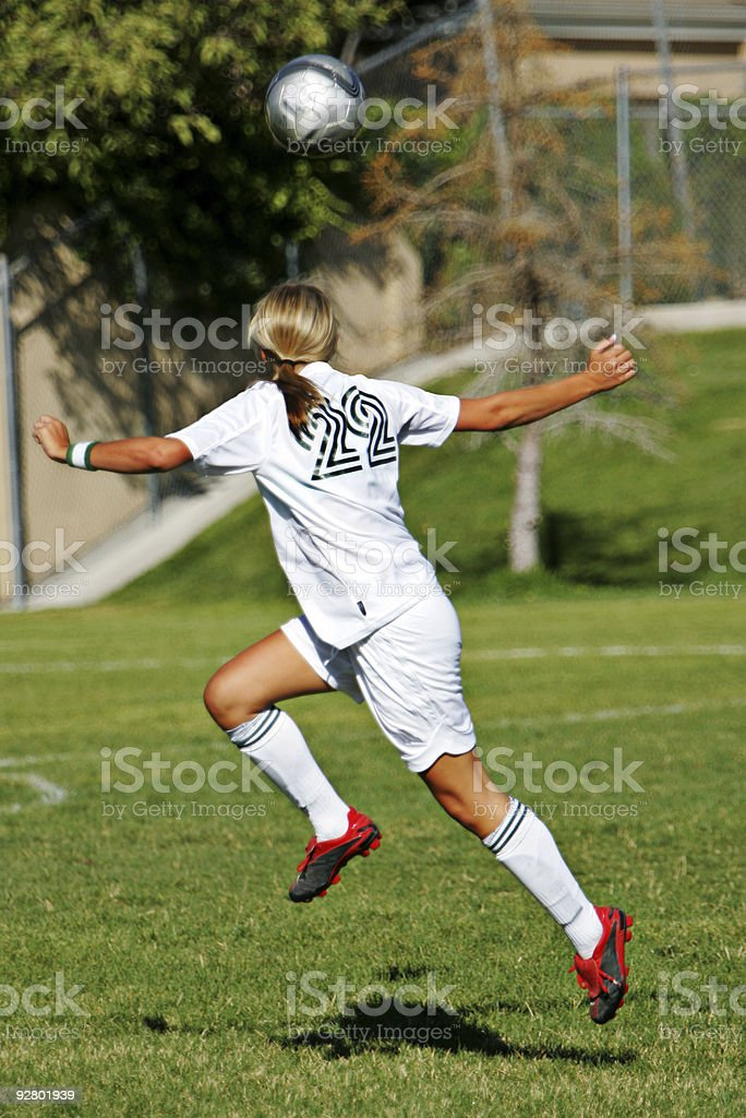 Attractive Female Soccer Player Positions Under Ball for Flying Header royalty-free stock photo