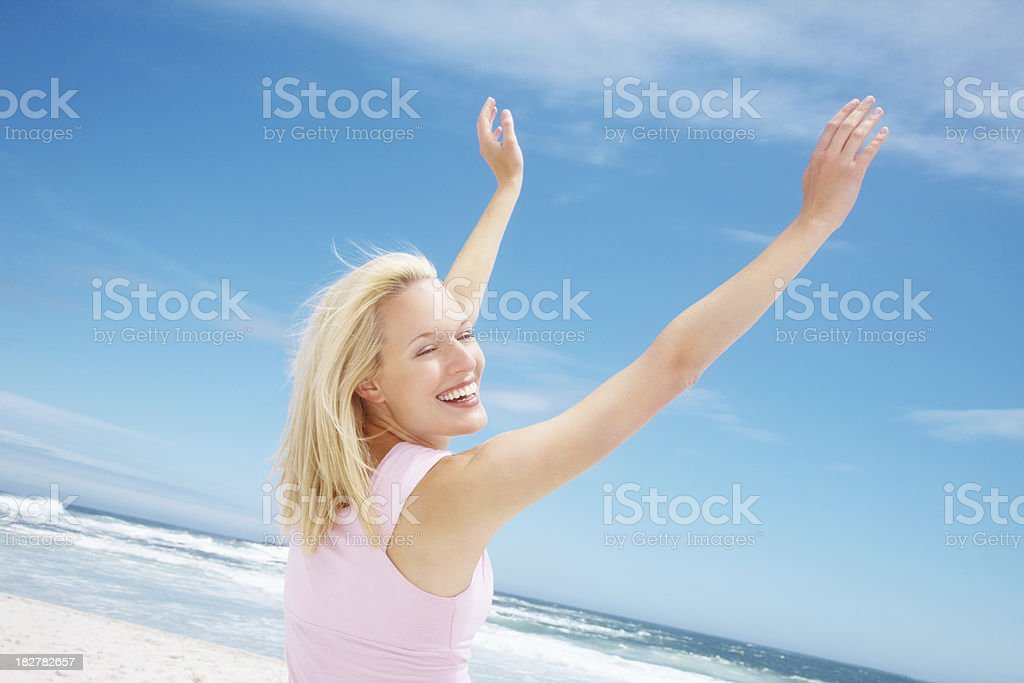 Attractive female standing on a beach with arms raised royalty-free stock photo
