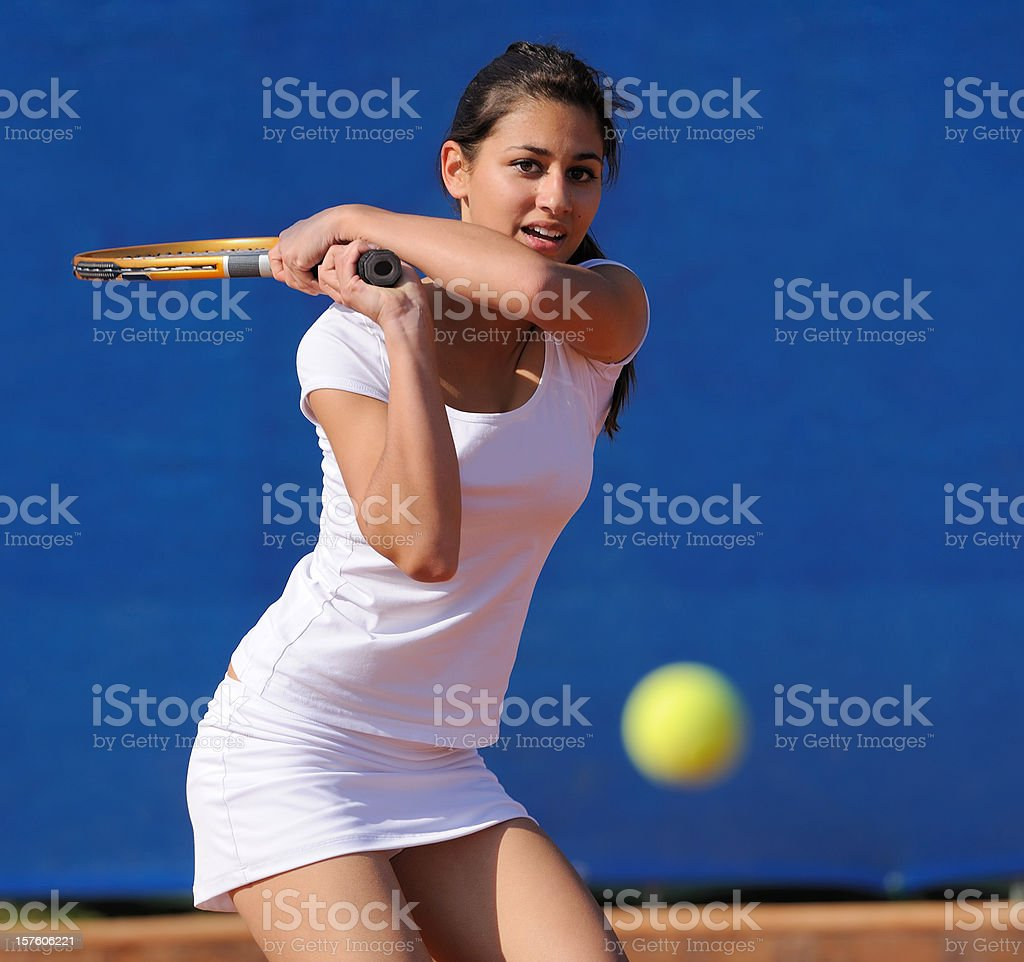 Attractive female tennis player hitting the ball royalty-free stock photo