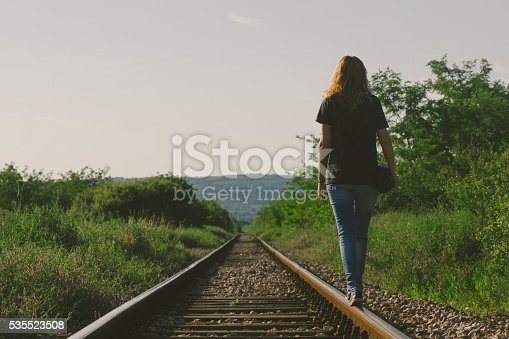 Attractive female walking down the railway in sunset. Photo is taken with dslr camera and telephoto lens in European countryside. Kodak portra filter applied in post processing to give vintage look.