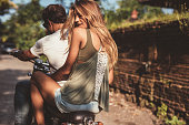 Rear view of attractive young female with her boyfriend on a motorcycle. Couple enjoying motorbike ride on countryside road.