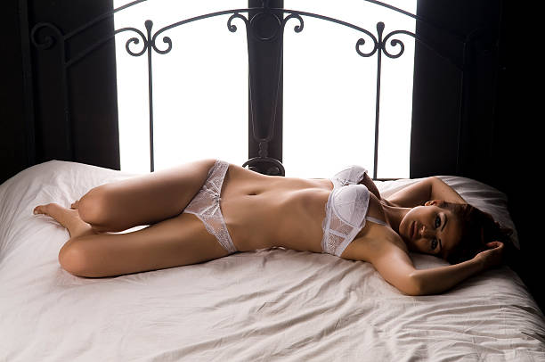 attractive female with lingerie on the bed - underwear stock photos and pictures