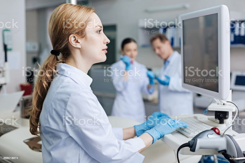 Attractive female worker typing text on computer stock photo