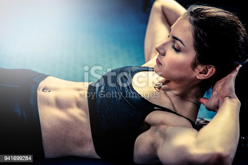 istock Attractive fit woamn working out abs in fitness gym, making ab intervals 941699284