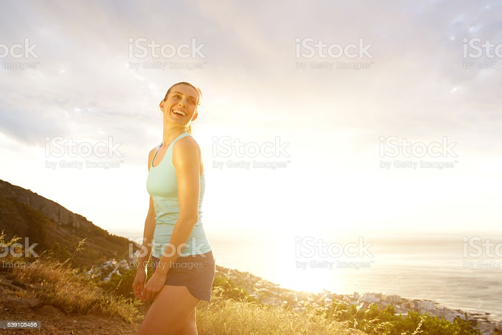 Attractive fit woman laughing outdoors stock photo
