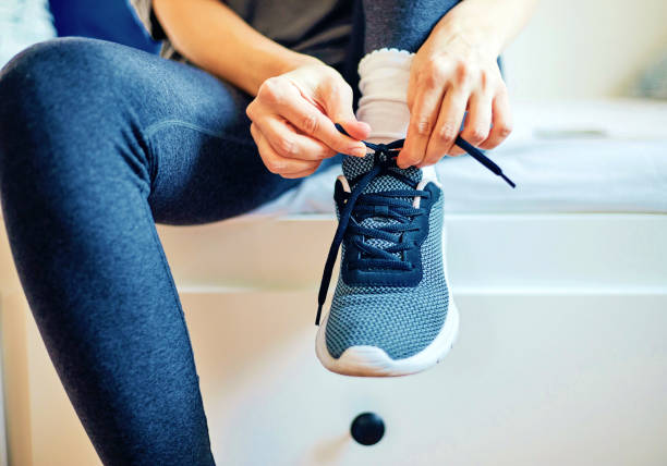Attractive fit woman tying shoe laces at home. stock photo