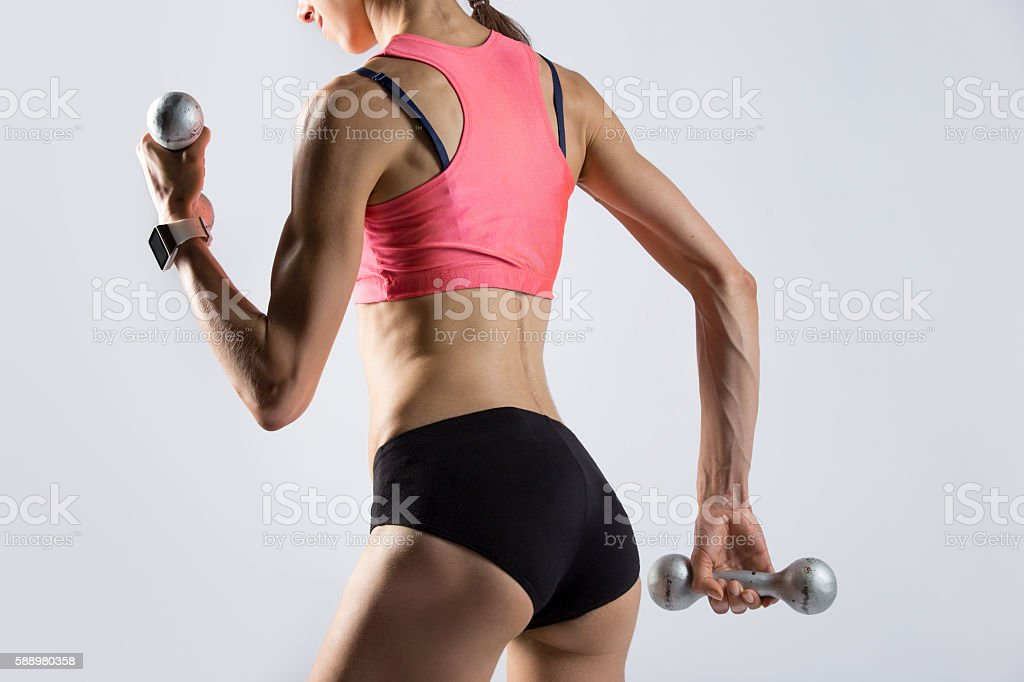 Attractive fit woman working out with dumbbells. Rear view stock photo