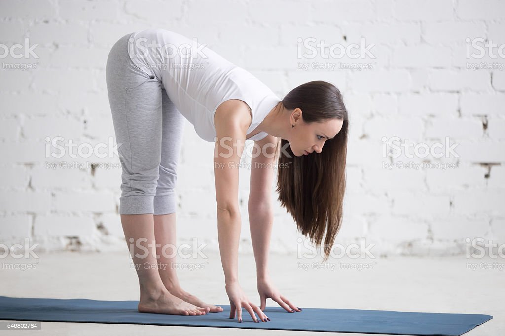 Attractive fit young woman doing Ardha Uttanasana pose in white stock photo