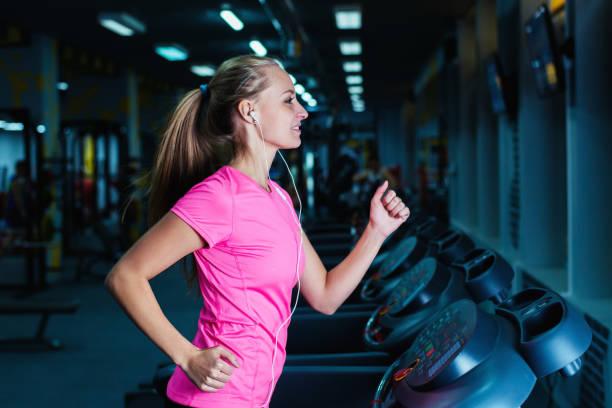 attractive fitness girl running on machine treadmill. - gewicht schnell verlieren stock-fotos und bilder