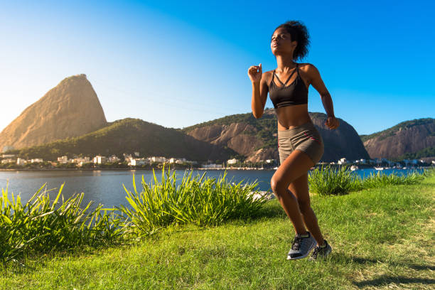 Attractive Fitness Woman Running in Meadow stock photo