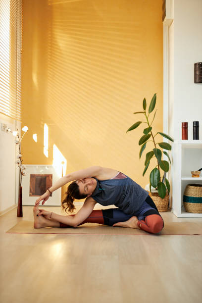 Attractive flexible caucasian yoga brunette in Revolved Head to Knee yoga pose. Home interior, morning time. stock photo