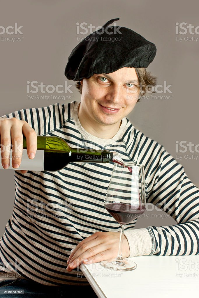 Attractive Frenchman pouring wine from bottle into glass stock photo