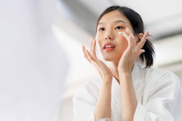 aantrekkelijke versheid aziatische vrouw schoon gezicht zoet water met zorg look te spiegelen in badkamer home achtergrond - korea stockfoto's en -beelden