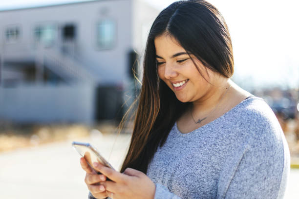 Attractive Generation Z Young Woman of Hispanic Ethnicity using a smart phone stock photo
